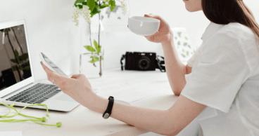 Mujer sentada en su escritorio bebiendo té y utilizando un teléfono móvil