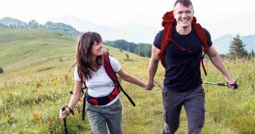 Pareja joven feliz mientras hace senderismo en la montaña