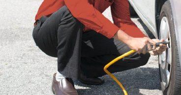 Hombre bombeando aire en los neumáticos de su coche