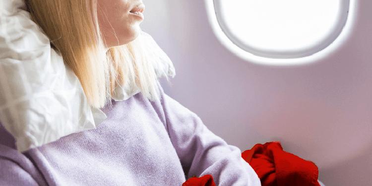 Mujer cansada que duerme en el asiento mientras viaja en avión