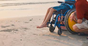 Chico joven en una silla de ruedas en la playa con su padre
