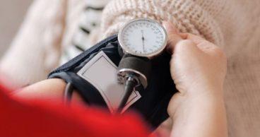 Un médico midiendo la presión sanguínea de una mujer