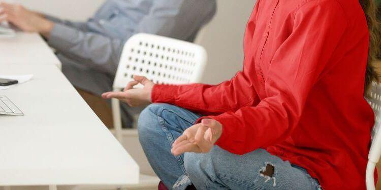 Mujer joven tomándose un descanso en la oficina para meditar
