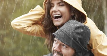 mujer recibiendo un piggy back bajo la lluvia