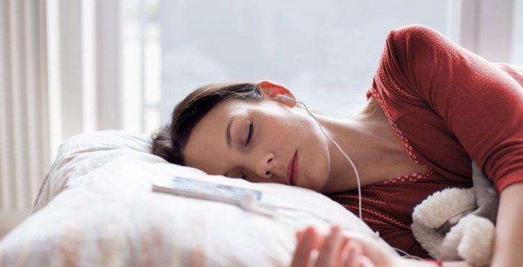 Una mujer durmiendo en la cama con auriculares y mejorando su descanso